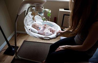 یک زن که در کنار گهواره مدرن نوزادش که درون گهواره خوابیده است ، نشسته