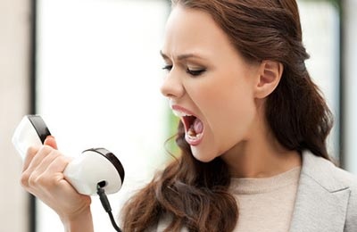 زن جوان و زیبا در حالی که به گوشی تلفن سیاه و سفیدی که در دست دارد نگاه میکند و فریاد میزند