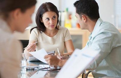 زن جوان در حال صحبت کردن با همکار خود در حالی که قلم و کاغذی در دست دارد و به او نگاه میکند