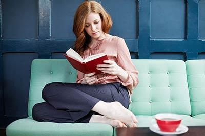 زن جوان با موهای قرمز در حالی که روی یک کاناپه آبی آسمانی نشسته و روی میز پیش رویش یک فنجان قرمز رنگ قرار دارد ، در حال خواندن یک کتاب با جلد قرمز است