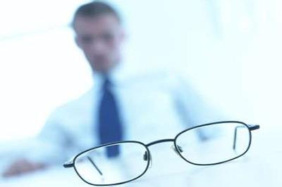 یک عینک با فریم فلزی سیاه رنگ و یک مرد در پس زمینه