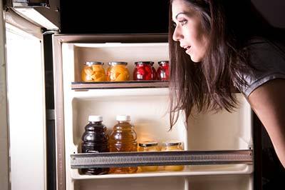 زن با موهای بلند در حال نگاه کردن داخل یخچال