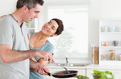 مرد با تیشرت طوسی روشن در حالی که تابه و قاشق در دستان خود دارد در حال اشپزی کردن است و زن با موهای کوتاه تیره در حالی که میخندد به مرد نگاه میکند