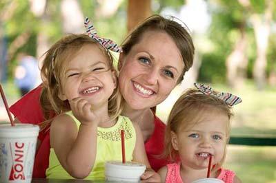 زن با دو کودک زیبا در کنارش در حال خندیدن