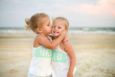 دو دختر خردسال در حالی که یکی دیگری را در آغوش گرفته و گونهاش را میبوسد و دیگری لبخند میزند