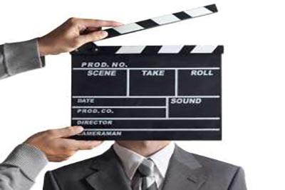 کلاکت فیلمبرداری جلوی صورت مردی با کت خاکستری