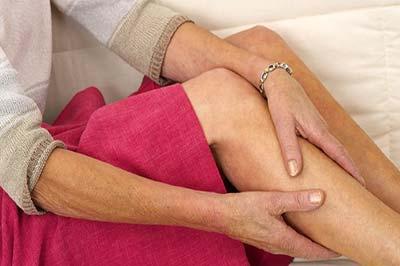 یک زن مسن با بلوز یاسی و دامن صورتی در حال ماساژ ساق پای راست خود