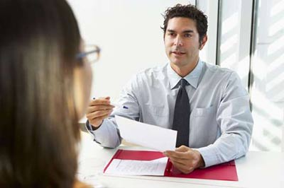 یک مرد با موهای تیره و پیراهن آبی و کراوات سورمه ای با یک خودکار و کاغذ در دست در حال حرف زدن با یک زن عینکی