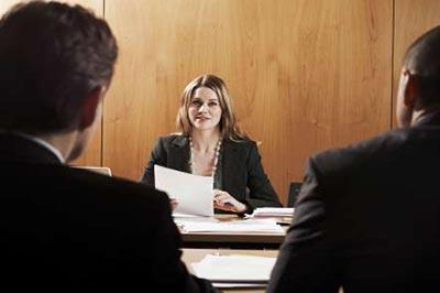 زنی با موهای بلند روشن و کت مشکی در حالی که کاغذی در دست دارد روبروی دو مرد نشسته است