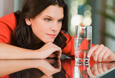 زن در حال نگاه کردن به لیوان آب نیمه پر