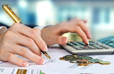 دستان یک زن که در حال حساب کردن با یک ماشین حساب و امضای یک بره است در حالی که تعدادی سکه در کنارش قرار گرفته است