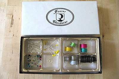 جعبه شکلات طوسی در حالیکه درون آن قرقره های سبز و آبی و صورتی و سیاه و زرد و طوسی و تعدادی سوزن ته گرد قرار دارد