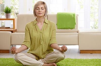 یک زن با موهای بلوند کوتاه و بلوز خردلی و شلوار کرم روی یک موکت مغز پستهای نشسته و با چشمان بسته در حال تمرکز کردن است