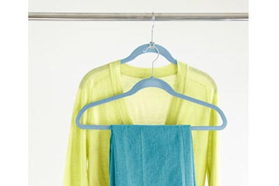 یک بلوز زرد و یک شلوار آبی که روی چوب لباسی های آبی رنگ آویزان شده اند