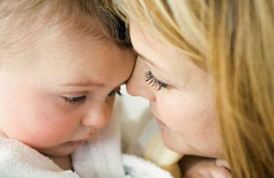 یک زن با موهای بلوند و یک کودک با موهای بلوند کم پشت در آغوشش