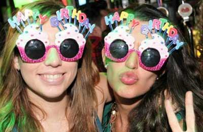 تصویر دو دختر جوان که عینکهای رنگی با نوشته تولدت مبارک به چشم دارند . یکی لبخند میزند و دیگری لبهای خود را غنچه کرده است