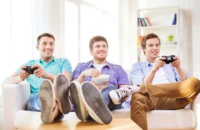 سه پسر جوان در حالی که روی کاناپه نشسته ومیخندند و دو نفر از آنها سرگرم بازیهای ویدئویی هستند و نفر وسط  کاسهای در دست دارد و در حال خوردن است