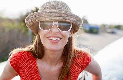 زن زیبا با موهای بلند قهوهای و یک کلاه حصیری و عینک افتابی به دوربین نگاه میکند و میخندد
