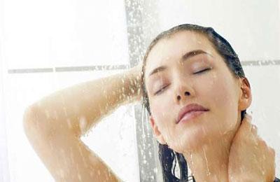 زن با موهای متوسط مشکی در حال آب کشی موها زیر دوش