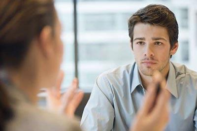 مردی جوان با موهای قهوهای و ته ریش با پیراهنی آبی در حال حرف زدن با یک زن