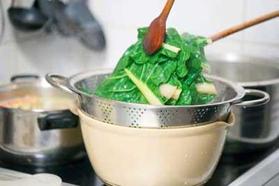 مقداری سبزی در حال ریختن داخل یک آبکش استیل که بر روی یک کاسه کرم رنگ قرار دارد