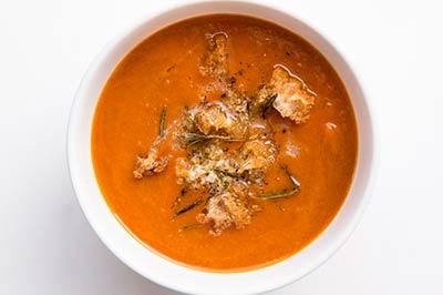 یک کاسه سفید رنگ که پر از سوپ گوجه است و روی آن چند تکه نان برشته گذاشته شده است