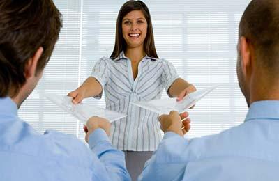 یک زن با موهای بلند در حال لبخند زدن به دو مرد با پیراهن های آبی ، کاغذهایی را می دهد