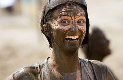 تصویر یک زن با چشمان طوسی و یک عینک بر روی سرش که سر تا پا گلی شده است و به شدت میخندد