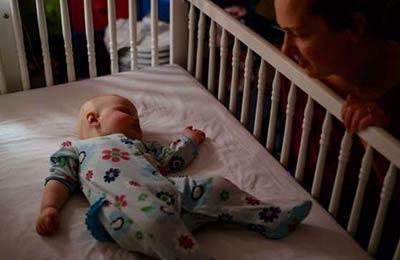 زنی کنار تخت نوزادش نشسته و به نوزاد که داخل تخت خوابیده نگاه میکند