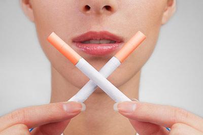 زن جوان و زیبا دو عدد سیگار را به صورت ضربدری روبروی صورت خود نگه داشته