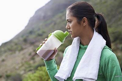 تصویر زن جوان زیبا در حالی که یک قمقمه نوشیدنی در دست دارد و حوله سفیدی روی گردنش است و به روبرو نگاه میکند