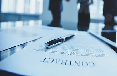 یک برگه کاغذ قرارداد روی یک میز شیشهای که یک گوشی موبایل در کنارش و یک روان نویسرویش قرار گرفته است