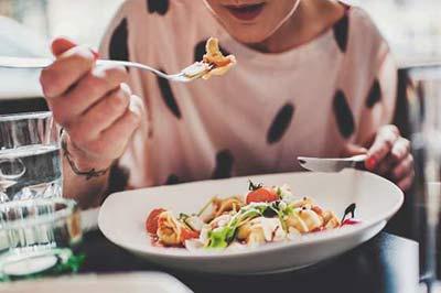 زن با کارد و چنگال در دست در حال خوردن غذا