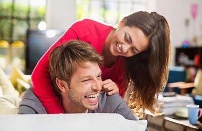 دختر جوان و زیبا  در حالی که می خندد دستانش را روی شانه مرد جوانی که نشسته و می خندد گذاشته است