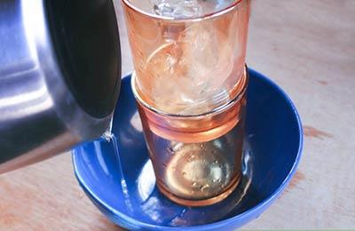 دو لیوان داخل هم که درون یک کاسه آبی رنگ گذاشته شدهاند و داخل یکی از آنها یخ ریخته شده است