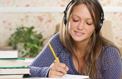 زن جوان و زیبا با هدفون روی سرش در حال نوشتن