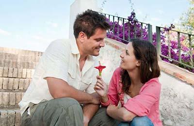 زن با موهای تیره و لباس صورتی و شلوار جین و مرد با پیراهن سفید و شلوار طوسی روی پلهها نشستهاند و زن در حال دادن شاخه گل قرمزی به مرد است