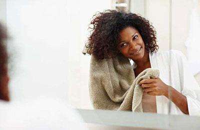 زنی سیاه پوست با موهای مجعد در حال خشک کردن موهایش با حوله