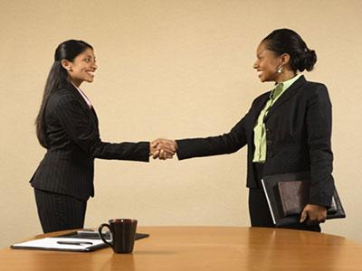 دو زن با لباس رسمی در حال دست دادن
