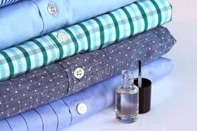 یک لاک ناخن شفاف در کنار چهار پیراهن آبی رنگ تا شده