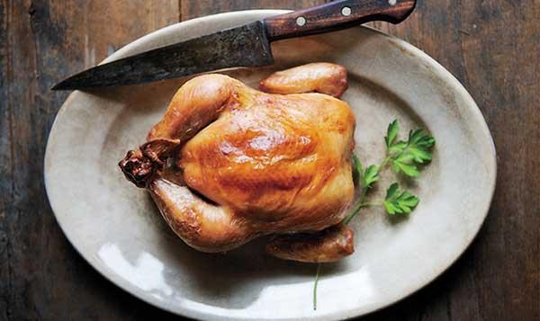 یک مرغ درسته بریان شده داخل یک دیس چینی و یک چاقو با دسته چوبی در کنارش