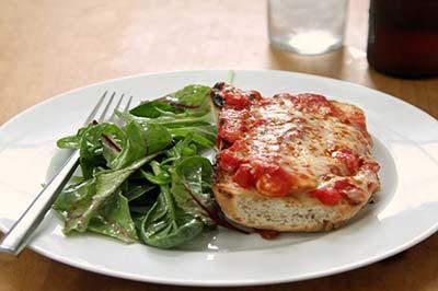 ساندویچ مرغ با پنیر روی یک بشقاب سفید که در کنار آن مقداری سبزی و یک چنگال نیز هست