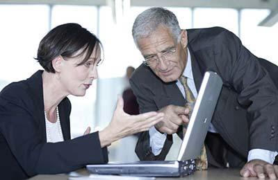 زن میانسال در حالیکه نشسته با همکار مرد خود که خم شده وبه لپتاپ نگاه میکند، صحبت میکند