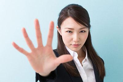 تصویر یک زن با چشمهای بادامی در حالی که دست راست خود را به علامت گفتن نه، بالا آورده