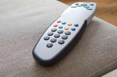 یک کنترل تلویزیون نقرهای و مشکی روی یک مبل طوسی