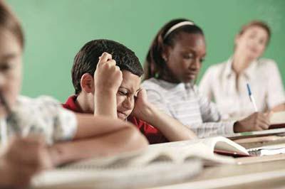 کودک در حال کتاب خواندن در حالی که ناراحت و مضطرب است