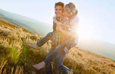 در یک دشت زیبا مرد جوان در حالی که زن را کول کرده و میخندد و زن نیز دستان خود را دور مرد حلقه کرده و می خندد