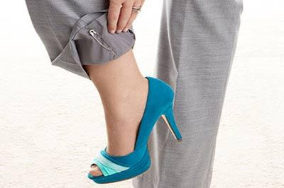 پای یک زن با یک کفش آبی و شلوار طوسی در حالیکه لبه شلوار را با دست تا زده است