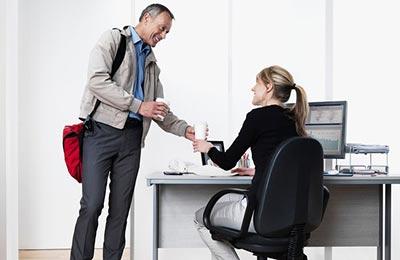 زن جوان روی صندلی نشسته و در حال گرفتن لیوان قهوه از مرد میانسال است