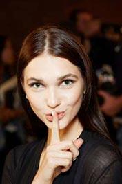 دختری با پوستی روشن وشفاف و موهای قهوهای بلند که انگشت اشاره دست راستخود را جلوی لبهایش قرار داده است